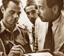 משה רוסנק, מפקד ההגנה ברובע חותם על הסכם כניעת הרובע. צילום: ג'ון פיליפיס