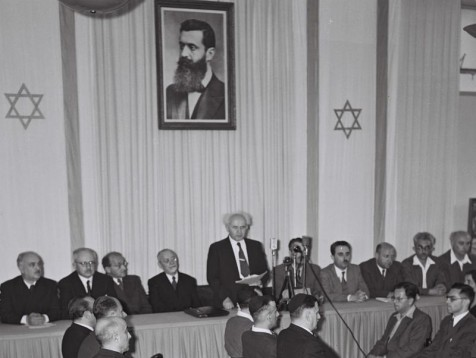 DAVID BEN GURION FLANKED BY MEMBERS OF HIS        PROVISIONAL GOVERNMENT READING THE DECLARATION OF           INDEPENDENCE & THE ESTABLISHED OF THE STATE OF ISRAEL.  טקס הכרזת העצמאות של מדינת ישראל במוזיאון תל אביב ברח' רוטשילד, תל אביב.         בצילום, ראש הממשלה דוד בן גוריון מקריא את מגילת העצמאות.
